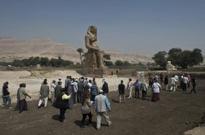 tourists-and-journalists-walk-past-a-newly-displayed-statue-of-pharaoh-amenhotep-iii-in-egypts-temple-city-of-luxor-on-march-23-2014